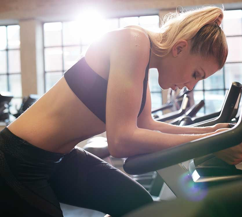 Woman Taking Break During Cycling Workout In Gym